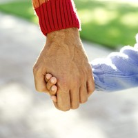 A man's hand holding a child's hand (close up)