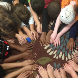 Students putting their hands in the middle of a circle