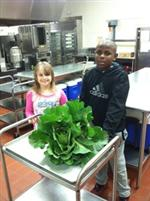 students showing off the cabbage grown in the garden