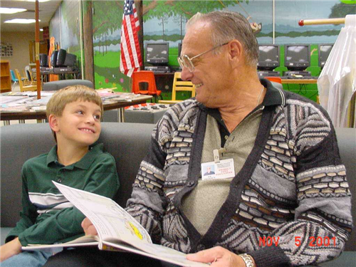 Gentlemen Mentor (right) working with a student (left) - Reading a book